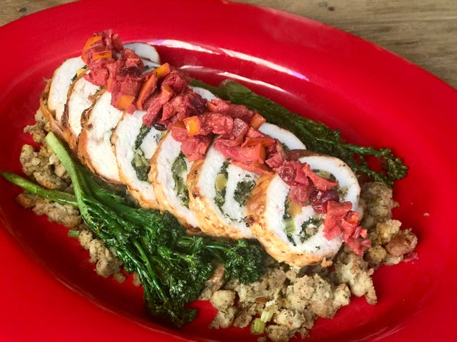 Slices of the rolled stuffed turkey breast are topped with cranberry and persimmon chutney and served over dressing with cooked broccoli rabe.