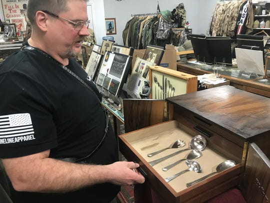 Craig Luther, owner of Military Connection in South Milwaukee, shows off a dinner service set owned by Adolf Hitler.