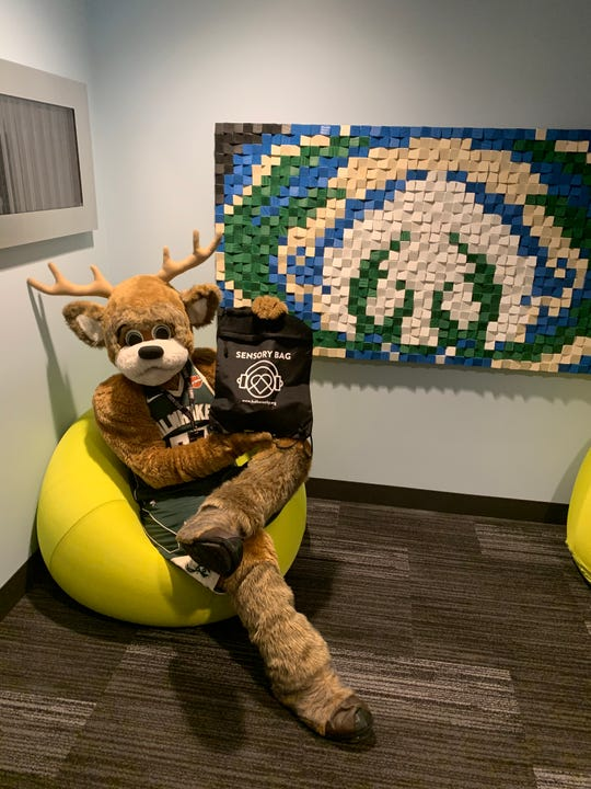Milwaukee Bucks mascot, Bango, holds a sensory bag while relaxing in one of the sensory rooms at Fiserv Forum.