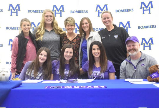 Mountain Home's Claudia Carter (front, second from left) signed a National Letter of Intent on Tuesday to play volleyball at the University of Central Arkansas. Pictured with Carter are: (front row) her sister Kendall Carter, her mother Kelly Carter, her father Glenn Carter; (second row) Junior Lady Bomber head coach Shelby Upshaw, Junior Lady Bomber assistant Shelby Anderson, Lady Bomber assistant Cathy Beckham, Carter's youth coach Bri Layton, and Lady Bomber head coach Jill Daves.
