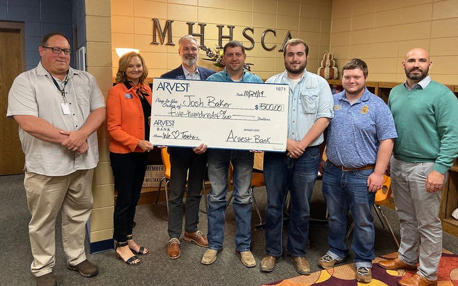 Mountain Home High School teacher Josh Baker was recently selected to receive a $500 grant from Arvest Bank as part of the We Heart Teachers campaign. The winning teachers will use their $500 awards toward enriching the classroom learning experience. The Arvest initiative to honor educators was launched on Oct. 7. Nominations were accepted via the Arvest Bank Facebook page. Pictured are: (from left) Brent Bogy, MHHS Principal; Sally Gilbert, Arvest; Kyle Davidson, Arvest; Baker; Carson White; Aaron Morris; and Dr. Jake Long, Superintendent, Mountain Home School District.