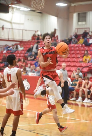 Norfork's Tyler Sorters knives between two Deer defenders for a layup in the Panthers' 63-57 win on Monday.