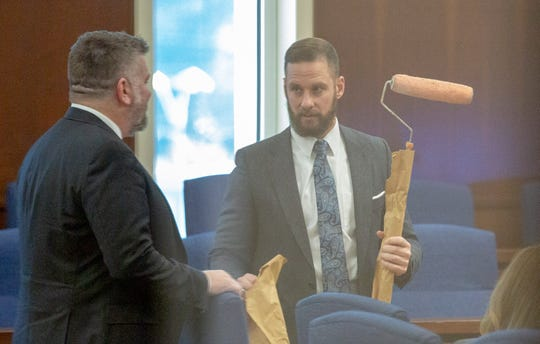 Prosecutor Ben McGough pulls out a paint roller, marked as evidence, ahead of opening arguments in the murder trial for officer A.C. Smith.