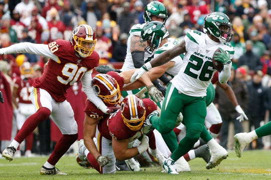 Nov 17, 2019; Landover, MD, USA; New York Jets running back Le'Veon Bell (26) carries the ball past the attempted tackle of Washington Redskins defensive end Matthew Ioannidis (98) in the second quarter at FedExField.