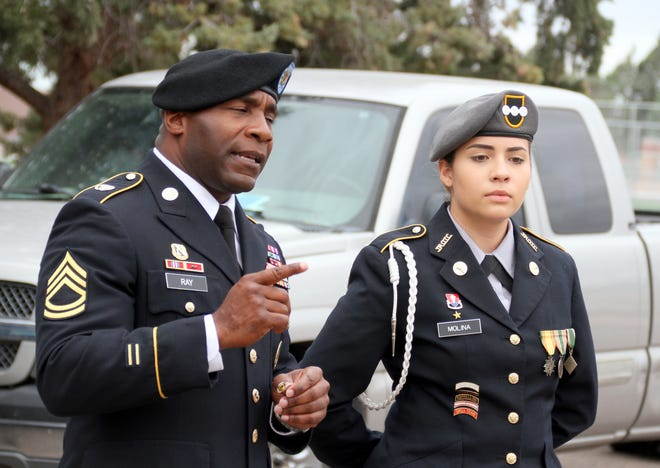 Cadet Lt. Col. Marianna Molina listens as Deming High School Army JROTC Sgt. 1st Class Chris Ray addresses cadets during last week's promotion ceremony on school grounds.