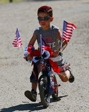 Jaydn Serna rides his bike, Monday, July 4, 2016 during Bloomfield's annual Fourth of July parade.