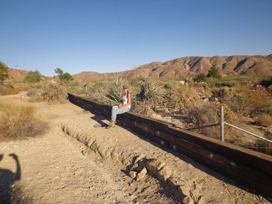 A simple 60-foot long railroad tie, flood wall pinned together with rebar with a diversion ditch to shunt lighter, more typical annual runoff back into the wash.