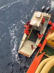 """A small boat, dubbed a """"tin can"""" is lowered into the water, loaded up with gear."""