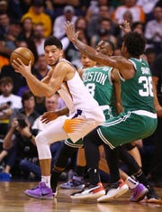 Phoenix Suns guard Devin Booker (1) is pressured by Boston Celtics guard Marcus Smart (36) in the first half on Nov. 18, 2019 in Phoenix, Ariz.