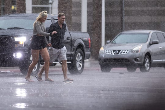 People cross the street in the rain on Tuesday, Nov. 19, 2019, in downtown Phoenix.