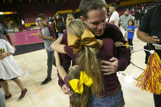 Roman Rozell (right) hugs his daughters following an ASU wrestling meet against Augustana at Desert Financial Arena in Tempe on Nov. 15, 2019. Rozell, a 35-year-old former Green Beret and Army combat veteran, is the oldest person to wrestle for ASU.