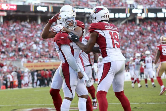 Arizona Cardinals quarterback Kyler Murray (1) is congratulated by teammates after rushing for a touchdown against the San Francisco 49ers in the fourth quarter at Levi's Stadium.