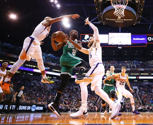Boston Celtics guard Kemba Walker (8) is pressured by Phoenix Suns guard Jevon Carter (4) and center Aron Baynes (46) in the first half on Nov. 18, 2019 in Phoenix, Ariz.