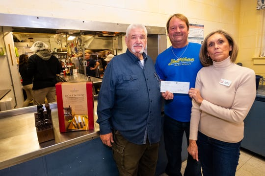 From left, Ron Anglebrandt and Bob Jury, both from the Blue Water Sportfishing Association, present new knives and a check for $500 to Mid City Nutrition Executive Director Alice Rieves Tuesday, Nov. 19, 2019.