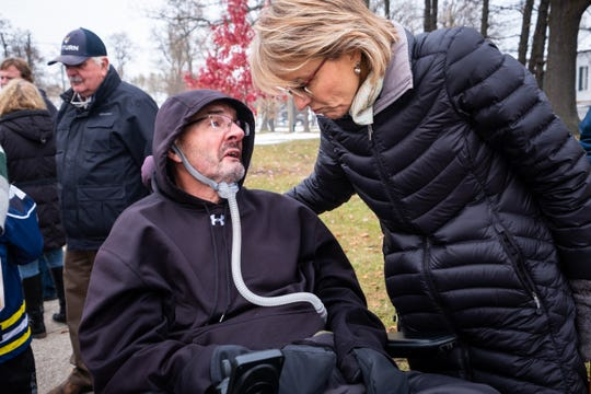 Gail Pagurko leans down to talk to her husband Frank Tuesday, Nov. 19, 2019, at Fort Gratiot Lighthouse. Frank was diagnosed with ALS in 2016.
