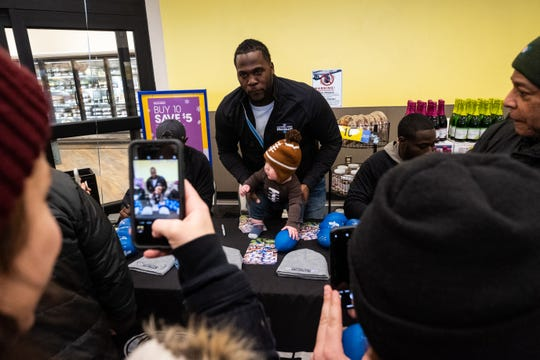Joique Bell, a former Detroit Lions running back, holds 8-month-old Jack Folsom for a photo during a meet-and-greet at Kroger in Port Huron Tuesday, Nov. 19, 2019. The event was part of the Football Week in Michigan Bus Tour's stop in Port Huron.