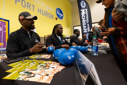From left, former Detroit Lions Herman Moore and Joique Bell, along with former University of Michigan quarterback Devin Gardner, sign autographs at Kroger in Port Huron Tuesday, Nov. 19, 2019. The event was part of the Football Week in Michigan Bus Tour's stop in Port Huron.