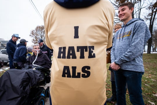 """Jim Frank wears a jersey with """"I hate ALS"""" written on the back while talking with people Tuesday, Nov. 19, 2019, at Fort Gratiot Lighthouse. Frank ran across Michigan to raise awareness and money for ALS research."""
