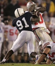 Ohio State quarterback Troy Smith, right, fumbles the ball as he is sacked by Penn State defensive end Tamba Hali, left, during the last minutes of the fourth quarter in this Saturday Oct. 8, 2005, file photo in State College, Pa. Penn State won, 17-10. (AP Photo/Carolyn Kaster)