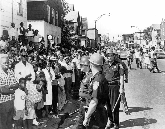 Crowds and police face each other in the street during the days of the 1964 Rochester riots.