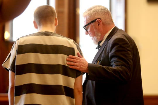 Defense attorney Martin Habekost puts his hand on the back of his client, Quinlyn Harden, 25, of Independence, during a sentencing after being found guilty of 29 counts of sexual abuse, rape, sodomy, attempted rape and unlawful sexual penetration at the Polk County Courthouse in Dallas on Nov. 18, 2019. Harden was sentenced to a total of 54 years and two months in prison for sexually abusing and raping five children at a Polk County day care run by his mother.