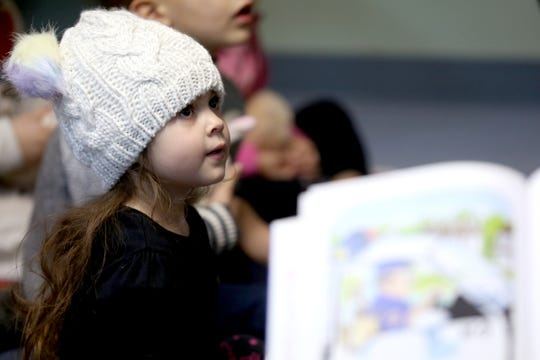 Violet Flores listens as police officers and others read to her pre-k class at the Oregon Child Development Coalition in Independence on Nov. 19, 2019. Local law enforcement agencies and education groups have released a report on the importance of access to pre-k in helping keep kids in school, succeed academically and stay out of crime later in life.