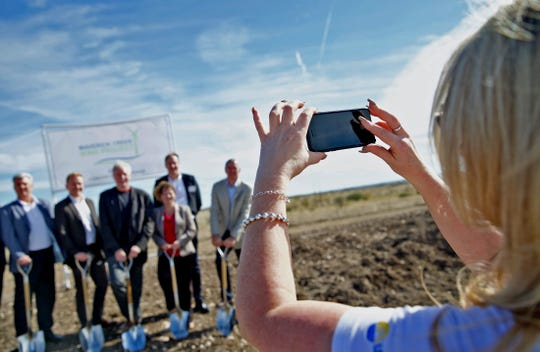 Stephanie Bose, director of corporate communications for Algonquin Power and Utilities Corp. at far right, takes a photo during the groundbreaking ceremony at the site of the Maverick Creek Wind Farm north of Eden on Tuesday, Nov. 19, 2019.