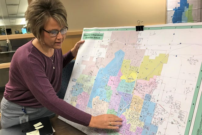 Sioux Falls School District spokeswoman DeeAnn Konrad shows off pushpins representing where applicants for a School Boundary Task Force live within the Sioux Falls School District. The task force will help shape plans for the district to redraw attendance zones next year.