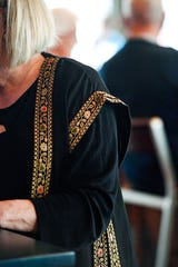 Christy Reiner wears a Palestinian garment she acquired from a family during a previous visit to the region on Sunday, Nov. 17, during a fundraiser at the Barrel House in Sioux Falls.