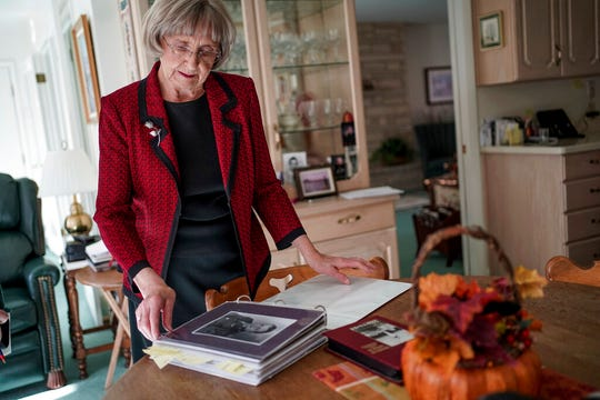 In this Thursday, Nov. 14, 2019, photo, Helen Lower Simmons looks through a binder of images, letters and documents that tell the story of her brother, Max Wendell Lower, while talking to journalists at her home in Logan, Utah. The remains of the solider reported missing in action during World War II will soon be returned to his family in Utah, thanks to DNA technology. (Spenser Heaps/The Deseret News via AP)