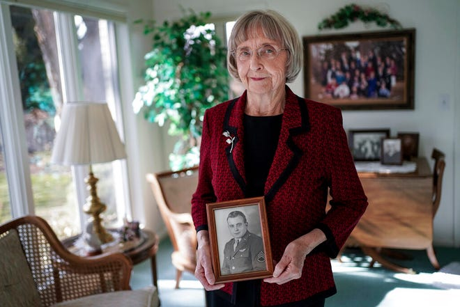 In this Thursday, Nov. 14, 2019, photo, Helen Lower Simmons poses for a portrait at her home in Logan, Utah, while holding a photograph of her brother, Max Wendell Lower, taken while he served in the Army Air Forces during World War II. The remains of the solider reported missing in action during World War II will soon be returned to his family in Utah, thanks to DNA technology. (Spenser Heaps/The Deseret News via AP)