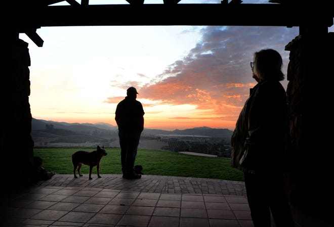 Chuck Carmichael, left, and his wife, Melinda Carmichael, enjoy a sunset from the backyard of their house in Tierra Rejada Valley near Simi Valley. The Easy Fire charged through their property Oct. 30, 2019, and they fought the flames around their home with garden hoses and a tractor. If it weren't for their brush clearance, they believe their home may have been lost.