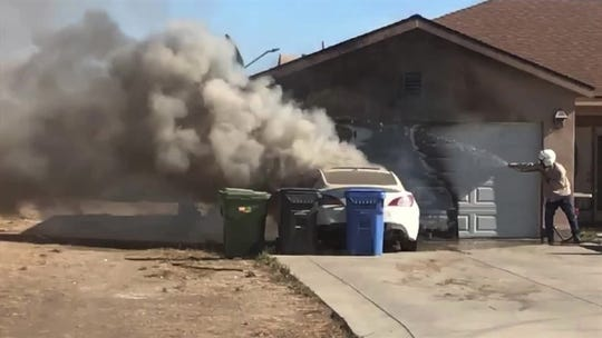 "Ryan ""Buster"" Brown douses a garage Monday to try to protect it from a car fire in the 10000 block of Citrus Drive in Moorpark."