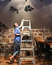 Anne Germain works on her mural at the Sawmill Brewing Company.