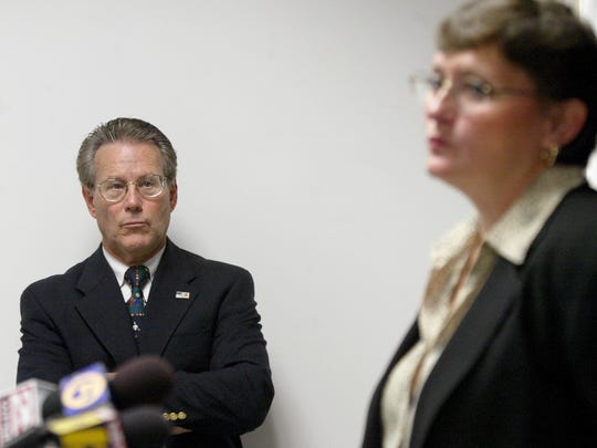 State Attorney Barry Krischer listens as Assistant State Attorney, Lanna Belohlavek, addresses the media about the grand jury's final report on the investigation of the Florida Institute for Girls.