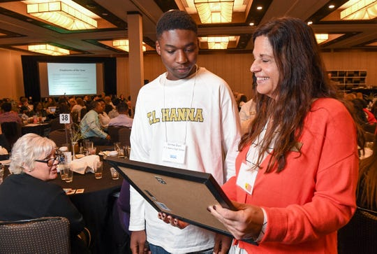 T.L. Hanna High School Special Education student Dontae Blunt, left, looks at the business of the year award with teacher Beth Hollingsworth during the Transition Alliance of South Carolina statewide conference at the Hyatt Regency in Greenville Wedesday. The three students demonstrated and sold their fragrant Fizzer Factory bath ball creations, a business they made at school and won the award for.