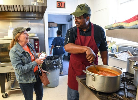 Joyce Grimmett, left, a volunteer with the Anderson Soup Kitchen, talks with cook Bobby Hardman, as he stirs soup for a lunch in November. He is retiring from his cook position December 31, but will help out.