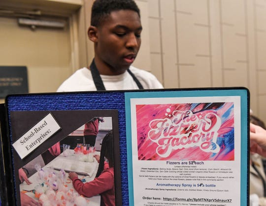 T.L. Hanna High School Special Education student Dontae Blunt stands by the Fragrant Fizzer Factory bath ball creation display during the Transition Alliance of South Carolina statewide conference at the Hyatt Regency in Greenville Wedesday. The T.L. Hanna High School students were recognized with the business of the year with their fragrant Fizzer Factory bath ball creations they sell.