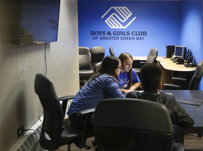Bay Port High School sophomore Michael Turull-Alvarez and freshman Natalee Libert get help with their homework from Bay Port's graduation specialist, Brittany Casanova at the Boys and Girls Club in Green Bay. The Boys and Girls Club's BE GREAT Graduate Program received a state grant to expand it statewide.