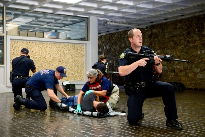 In this file photo from a drill in 2016, Asheville police officers Josh Hill, left, Jessica McCoy, back, and Sean Davis secure the area, allowing Rob Birchfield, with the Asheville Fire Department, center left, and Terri Arrwood, with Buncombe County EMS, to treat police trainee Eduardo Hernandez for a simulated injury.  In the current budget, Asheville has nearly 1,300 Full Time Equivalent employee positions, and Buncombe County listed 1,634 workers.
