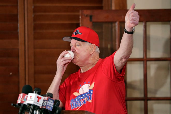 Pat Williams, co-founder of the NBA Orlando Magic basketball team, kisses a baseball at a news conference to announce a campaign to bring a Major League Baseball team to Orlando, Wednesday, Nov. 20, 2019 in Orlando. Williams brought good luck to the Orlando Magic by kissing ping pong balls before the NBA draft two years in a row bringing the number one picks twice.