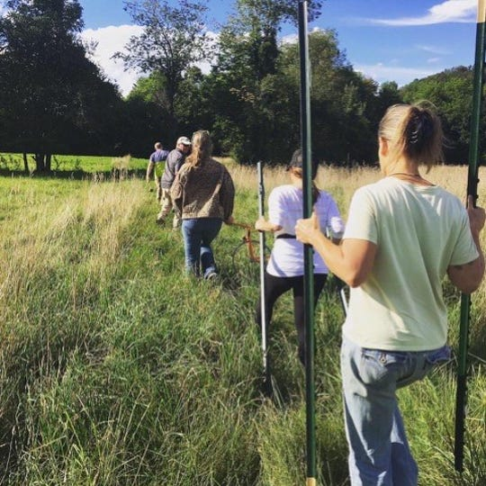 A group of volunteers helps Shawn Smith and her wife, Melissa Hoffman, post nearly 1300 acres of land in Huntington, owned by their nonprofit called Foundation For A Sustainable Future
