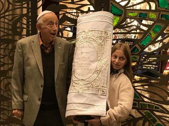 Campbell  Schwarz holds a furled and newly covered 200-year-old Holocaust-surviving Torah that she raised money to restore for her bat mitzpha at Congregation Beth El in Voohees.