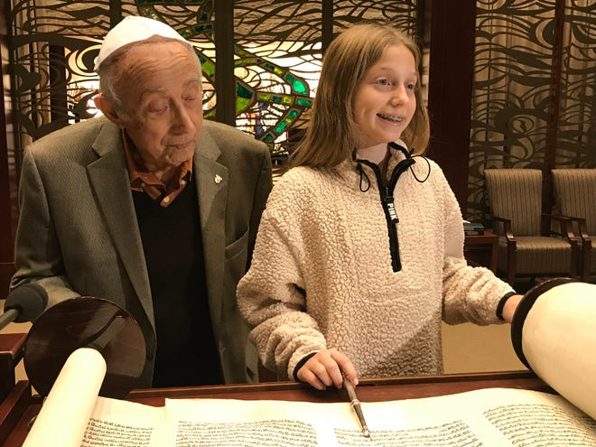 Campbell Schwarz helped to restore and write in this 200-year-old Torah, which survived the Holocaust, as her coming-of-age project at Congregation Beth El in Voorhees. Holocaust survivor and congregation member Fred Behrend views the Torah, which was used this month in celebrating his 80th bar mitzvah anniversary.