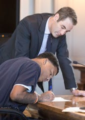 Terell Nesbitt signs court documents before his plea of guilty to drug charges in three separate incidents inside Judge Michael Ater's courtroom on Nov. 20, 2019.