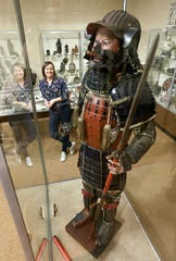 Jennifer Bush is the director of the Johnson-Humrickhouse Museum in Coshocton. She is pictured with the museum's Japanese Samurai armor.