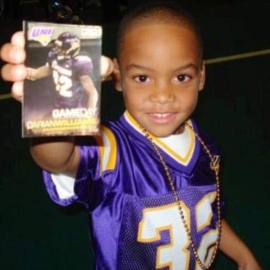 Jayden Williams holds up a playing card featuring his father, Darian Williams. Darian played football for Northern Iowa from 2006-07. Jayden now plays running back for West Des Moines Valley.