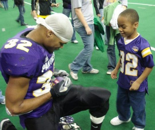 A young Jayden Williams, right, eagerly watches his dad, Darian, sign a football after a Northern Iowa football game in 2006. Darian Williams played for Northern Iowa from 2006-07. Jayden Williams now plays for West Des Moines Valley.