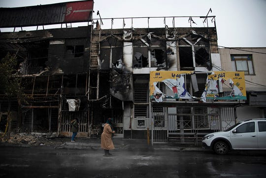 In this photo taken Monday, Nov. 18, 2019, and released by Iranian Students' News Agency, ISNA, people walk past buildings which burned during protests that followed the authorities' decision to raise gasoline prices, in the city of Karaj, west of the capital Tehran, Iran.