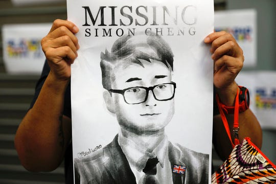In this Aug. 21, 2019, file photo, a supporter holds a poster outside of the British Consulate in Hong Kong during a rally in support of an employee of the consulate who was detained while returning from a trip to China.